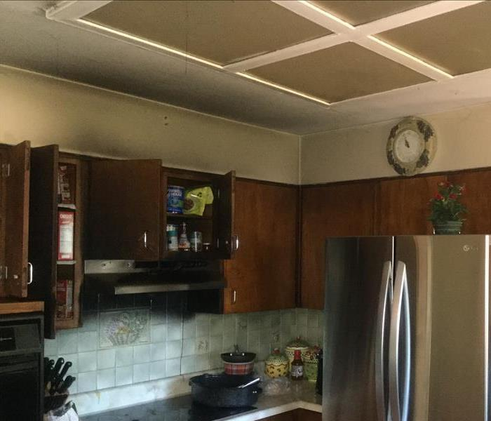 A kitchen with black soot damage above the stove, on cabinets, and on the ceilings
