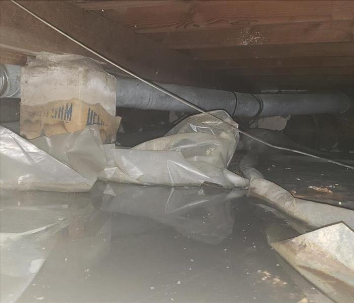 Crawl space flooded with standing sewage water.