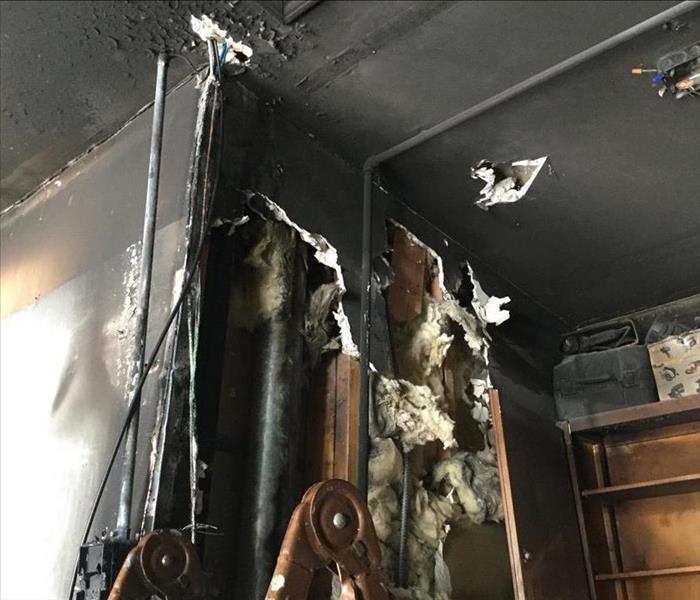 Drywall in a garage that has been severely damaged by fire