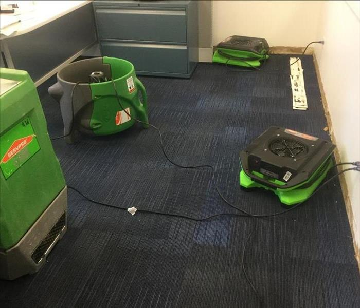 Three fans and a dehumidifier set up to dry wet carpeting