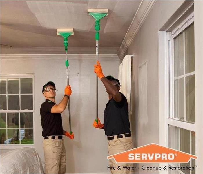 SERVPRO technicians using sponges on poles to clean a ceiling damaged by soot.