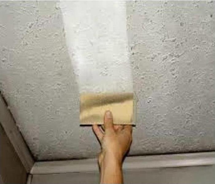 A hand wiping a dry sponge across a soot-stained wall, leaving a clean trail