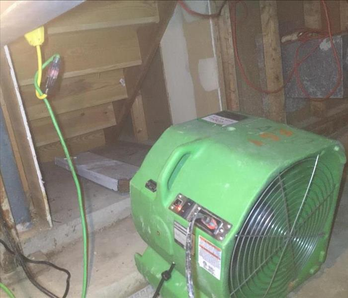 A large green fan drying out underneath a wet staircase