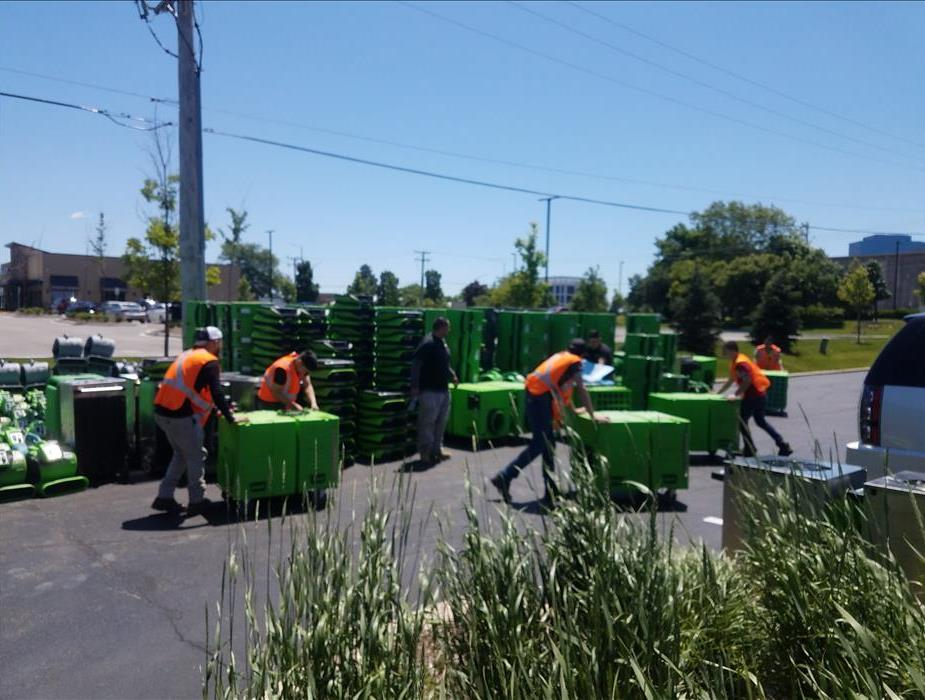 Workers in orange jackets moving large stacks of green drying equipment