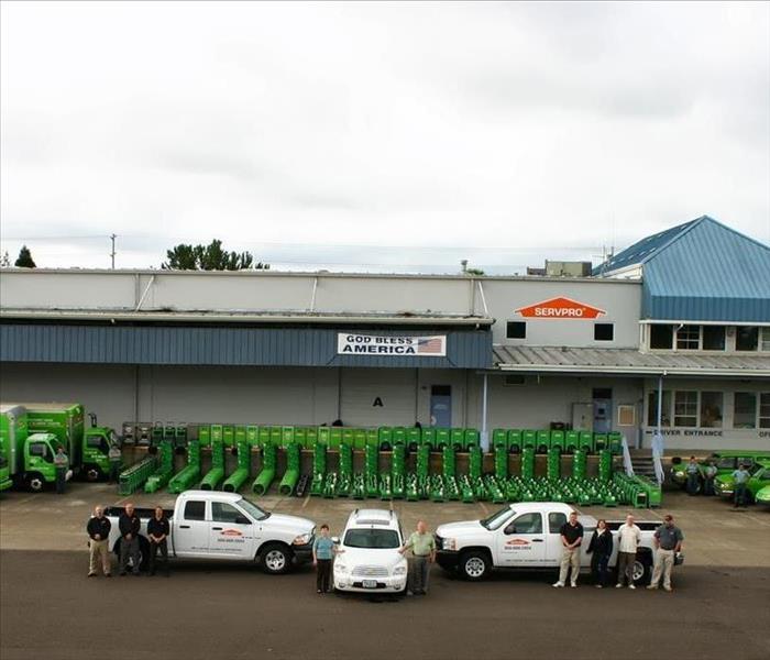 A building with stacks of green drying equipment and vehicles in front and a group of people posing